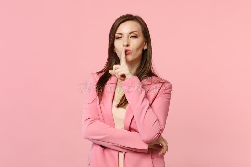 El retrato de la mujer joven bonita en chaqueta que dice silencio sea reservado con el finger en gesto de los labios shhh aislado fotografía de archivo libre de regalías