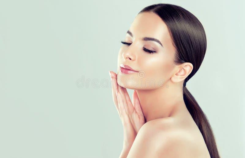 El retrato de la mujer joven con la piel fresca limpia y suaves, delicados componen La mujer está tocando a propia cara blando fotos de archivo libres de regalías