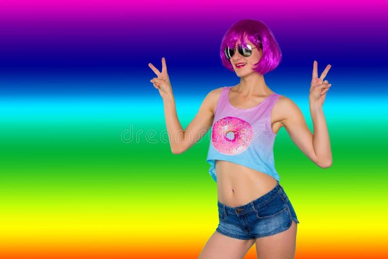 El retrato de la mujer joven del transexual en peluca y gafas de sol rosadas muestra la muestra de la victoria en fondo del arco  foto de archivo