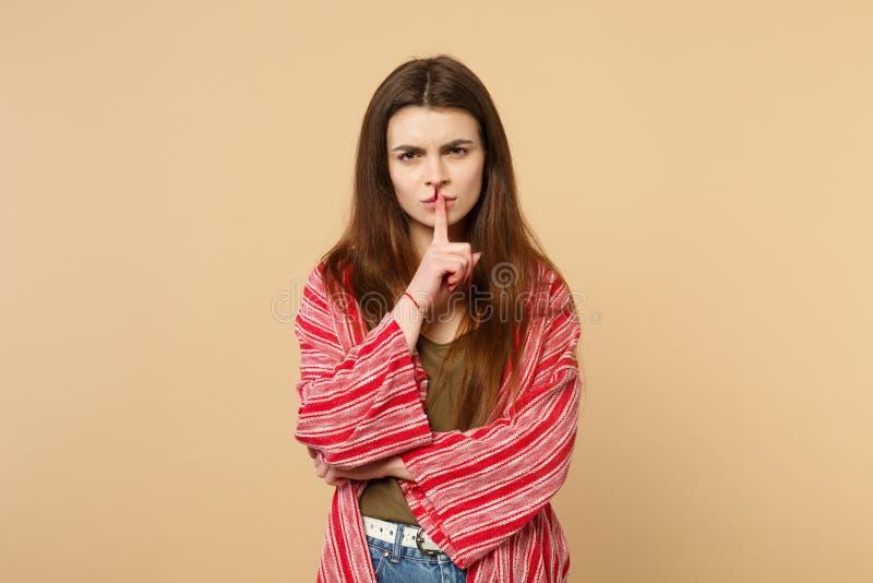 El retrato de la mujer joven en ropa casual que dice silencio sea reservado con el finger en gesto de los labios shhh aislado en  fotos de archivo libres de regalías