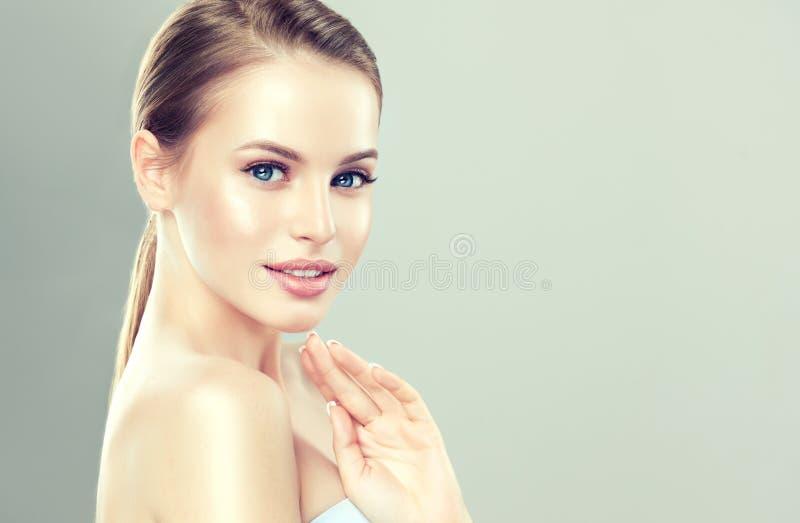 El retrato de la mujer joven, encantadora con el peinado recolectó en el manojo El modelo con la piel fresca limpia y suaves, del foto de archivo