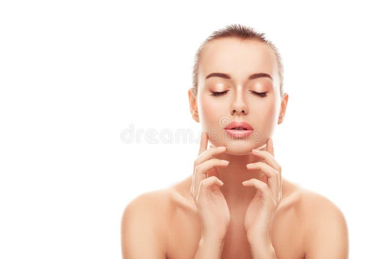 El retrato de la mujer joven hermosa con la piel limpia, fresca toca su cara en fondo blanco aislado fotografía de archivo libre de regalías