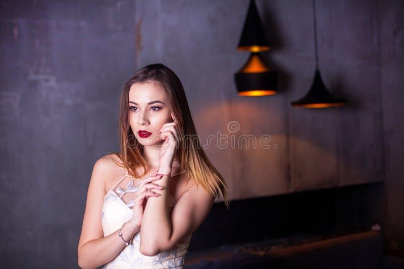 El retrato de la mujer joven hermosa con maquillaje en la moda viste vestido de noche de la mujer que lleva atractiva con decolle imagen de archivo