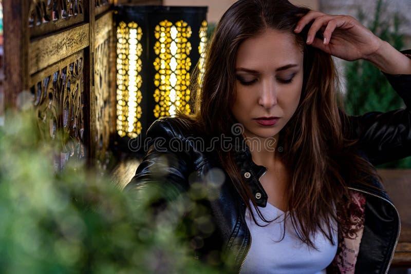 El retrato de la mujer joven hermosa con el pelo marrón se está sentando cerca de la lámpara y está mirando abajo fotos de archivo libres de regalías
