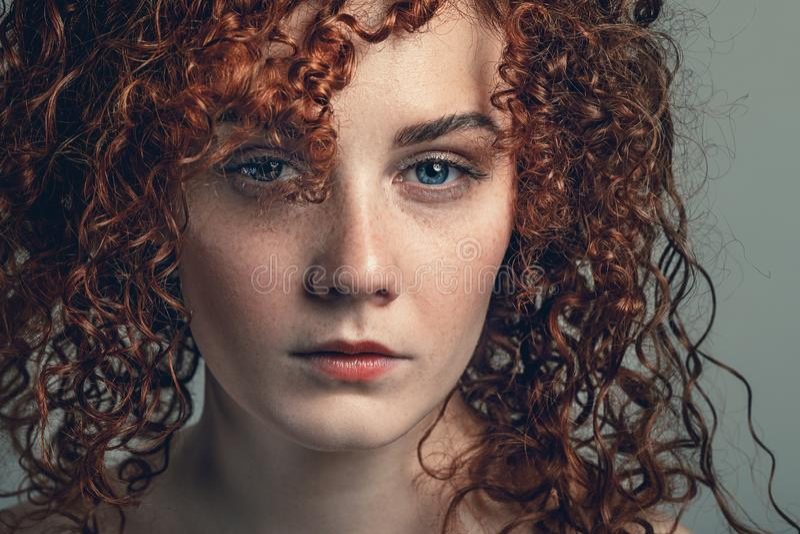 El retrato de la mujer joven hermosa con el pelo rizado, se cierra encima de la visión imagen de archivo
