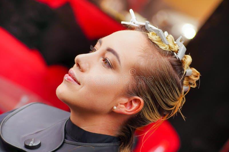 El retrato de la mujer joven hermosa que se sienta en un salón de pelo, alista para un nuevo estilo de pelo en un fondo borroso imagenes de archivo