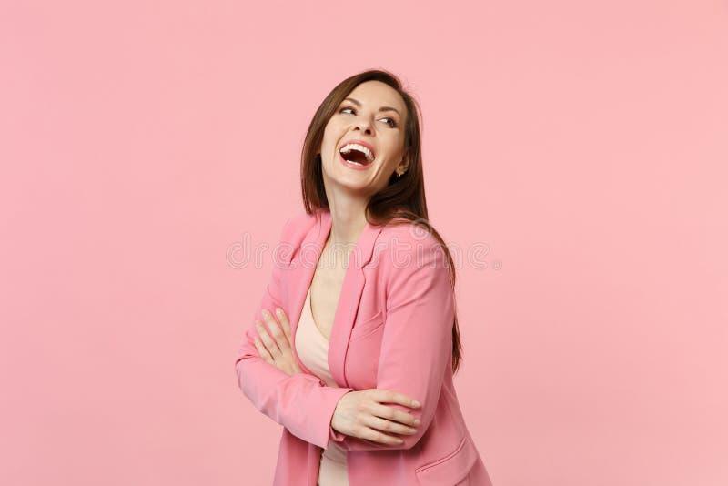 El retrato de la mujer joven de risa alegre en la chaqueta que se colocaba, llevando a cabo las manos dobló aislado en la pared r imagen de archivo