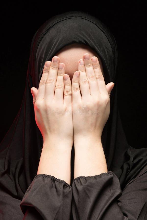 El retrato de la mujer musulmán joven seria hermosa que lleva el hijab negro con las manos acerca a su cara como concepto de roga fotos de archivo libres de regalías
