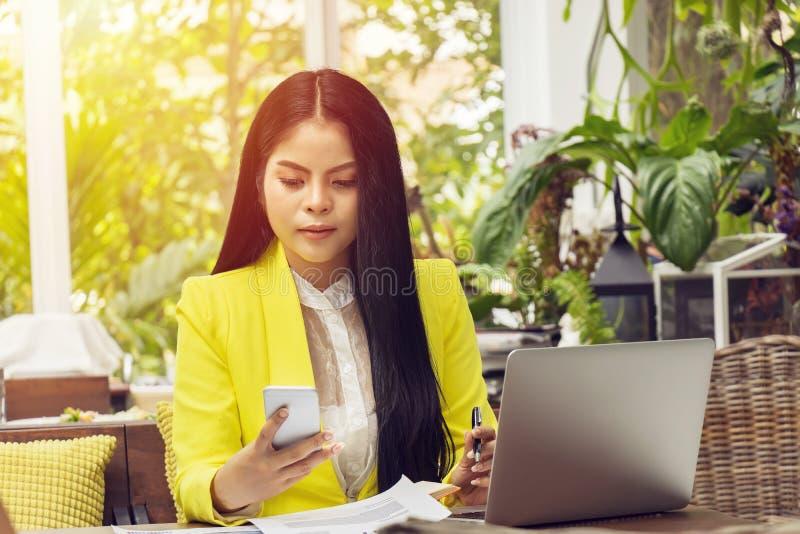 El retrato de la mujer de negocios asiática hermosa y confiada en el trabajo con el ordenador portátil y el teléfono del cuaderno foto de archivo