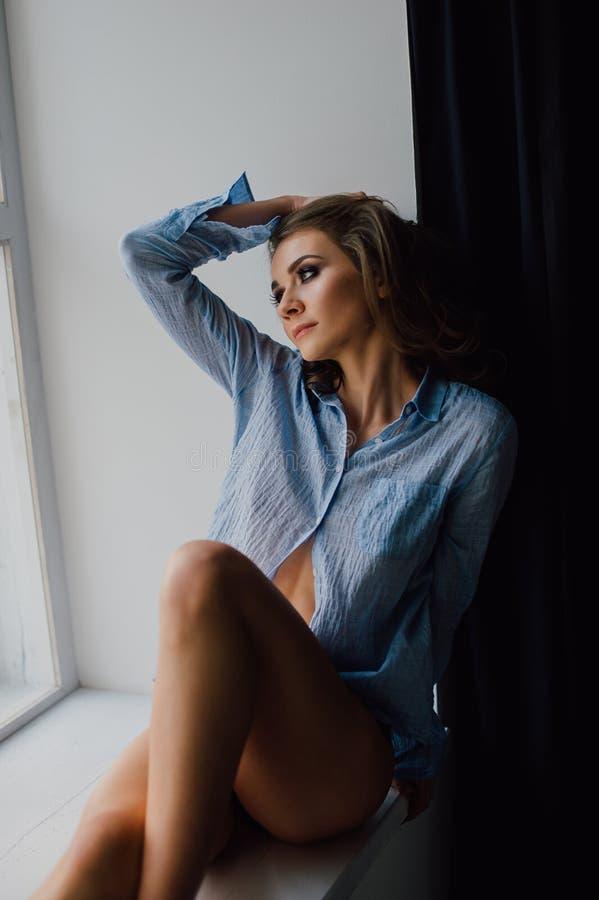 El retrato de la mujer positiva joven atractiva que presenta en estudio en la luz natural, camisa azul que lleva, tiene ajuste bu foto de archivo libre de regalías
