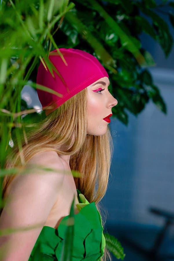 El retrato de la mujer rubia atractiva hermosa atlética con compone en casquillo y traje de la nadada en la piscina imagenes de archivo