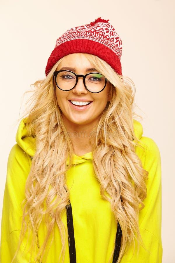 El retrato de la mujer rubia caucásica feliz con las gafas redondas, lleva el casquillo rojo y la camiseta amarilla colorida, tie fotografía de archivo libre de regalías