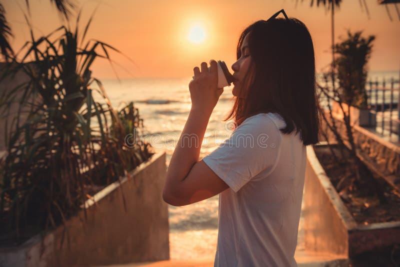 El retrato de la mujer se está relajando en el verano de la duración de la playa mientras que café que bebe, silueta de la relaja imagen de archivo