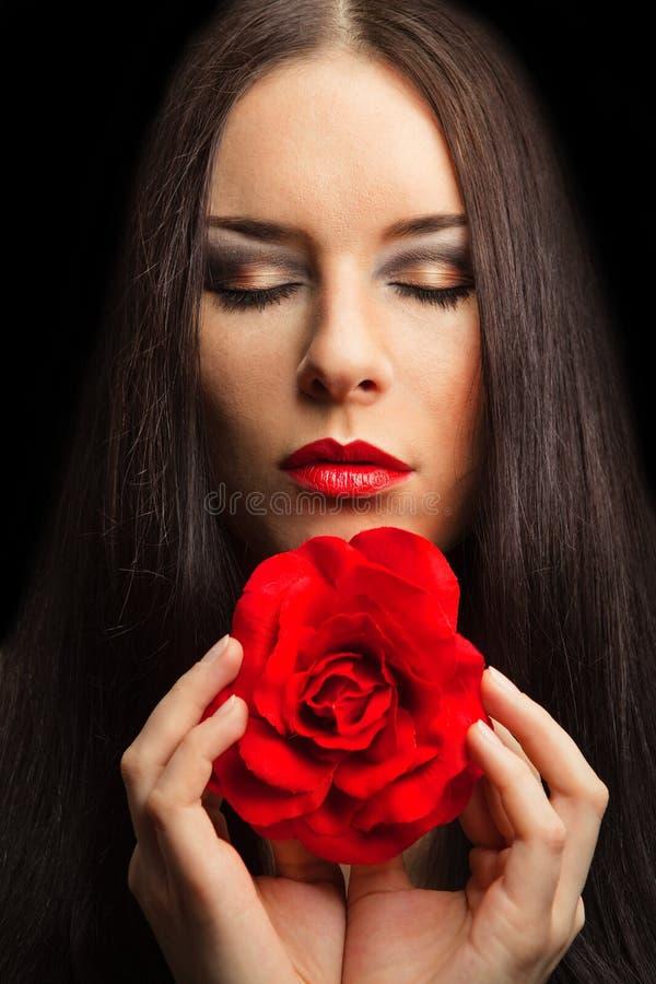 El retrato de la mujer triguena hermosa con rojo se levantó fotografía de archivo libre de regalías