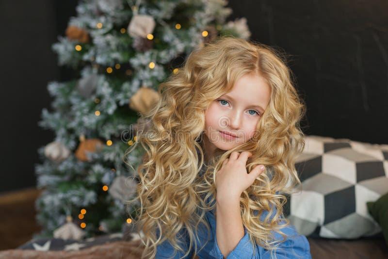 El retrato de la niña bastante rubia se sienta y toca el pelo en una cama en tiempo de la Navidad imagen de archivo