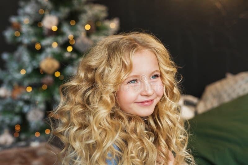 El retrato de la niña bastante rubia sonríe y parece lateral en tiempo de la Navidad imagenes de archivo