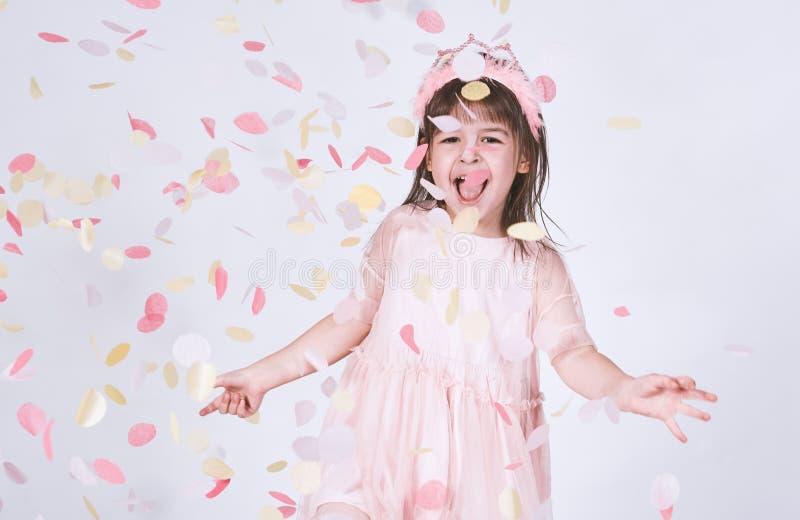 El retrato de la niña que lleva el vestido rosado en Tulle con la corona de la princesa en la cabeza en el fondo blanco goza de c imagen de archivo
