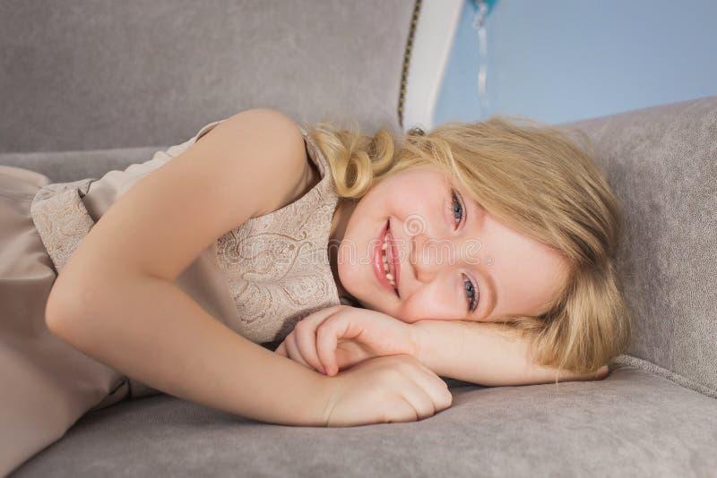 El retrato de la niña rubia miente en un sofá foto de archivo