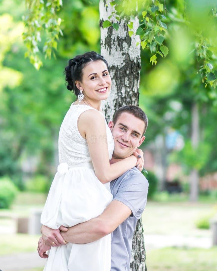 El retrato de la novia femenina de los pares jovenes y el novio del varón que abraza en verano parquean Sirva la esposa criada ma imágenes de archivo libres de regalías