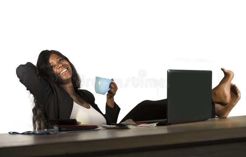 El retrato de la oficina de la forma de vida de la empresaria afroamericana negra feliz y atractiva joven con los pies en la sonr fotos de archivo libres de regalías