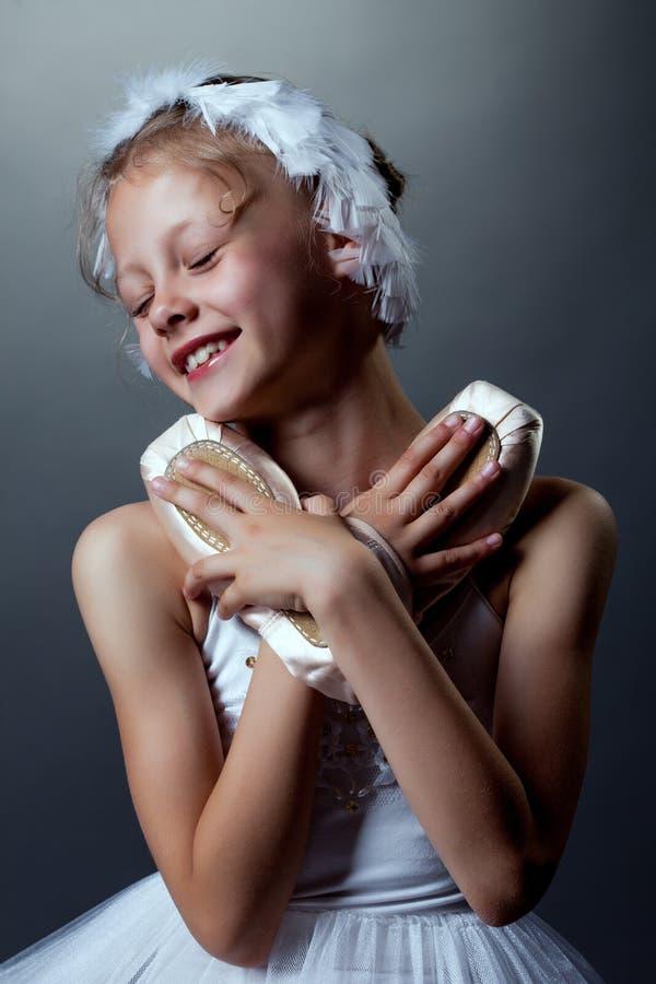 El retrato de la pequeña bailarina feliz abraza pointes imagen de archivo libre de regalías