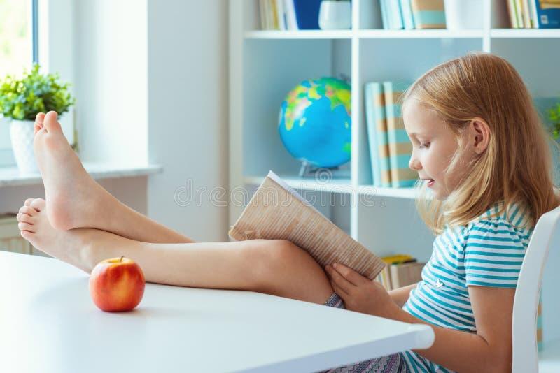 El retrato de la pequeña colegiala divertida que se relaja lee el libro en foto de archivo libre de regalías