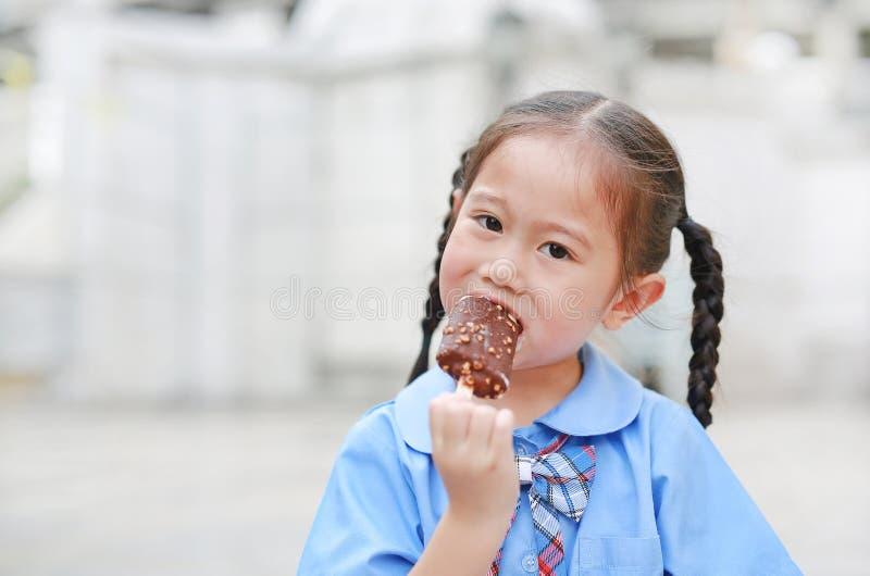 El retrato de la pequeña muchacha asiática del niño en uniforme escolar goza el comer del helado sabroso de vainilla del chocolat imágenes de archivo libres de regalías