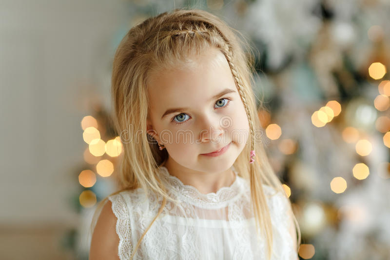 El retrato de la pequeña muchacha rubia hermosa, árbol de navidad enciende i fotos de archivo