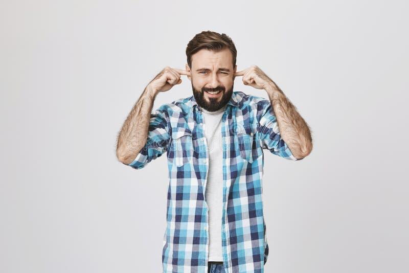 El retrato de la persona enfadada e infeliz que bizquea ojos y cubre los oídos con los dedos índices debido a fuerte ruido fotografía de archivo
