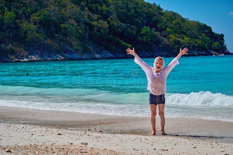 El retrato de la vista delantera un muchacho feliz que respira el aire fresco profundo y outstretching los brazos con el mar trop foto de archivo