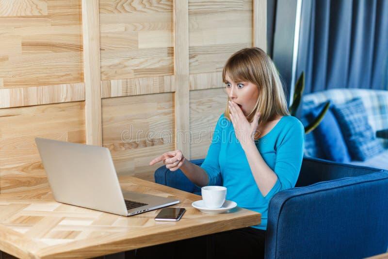 El retrato de la vista lateral de la chica joven increíble con el pelo rubio en camiseta azul se está sentando en café, está trab imágenes de archivo libres de regalías