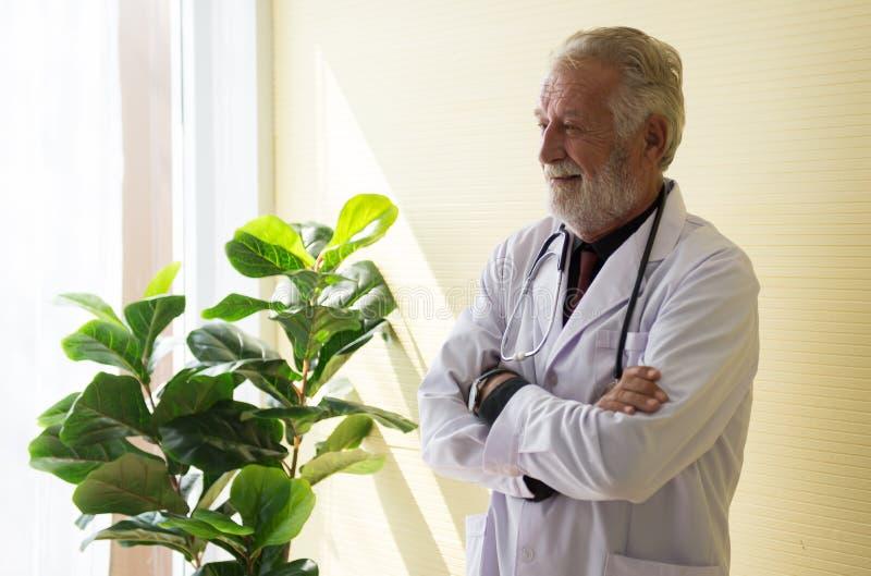 El retrato de los brazos derechos y cruzados mayores del doctor en la actitud de pensamiento del hospital, feliz y positiva, copi foto de archivo libre de regalías