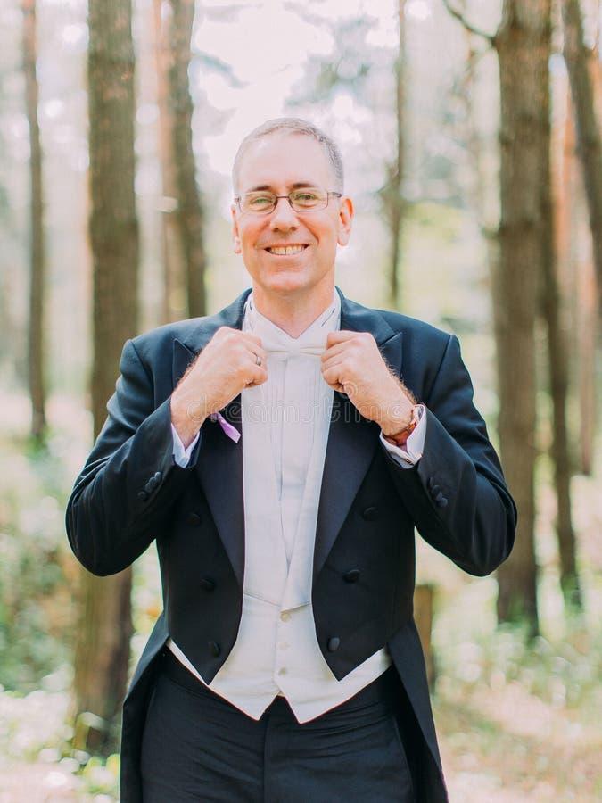 El retrato de medio cuerpo del novio alegre corrige su corbata de lazo blanca Ubicación del bosque fotos de archivo libres de regalías