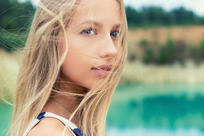 El retrato de muchachas atractivas hermosas con los labios llenos y el pelo rubio se coloca cerca del lago foto de archivo