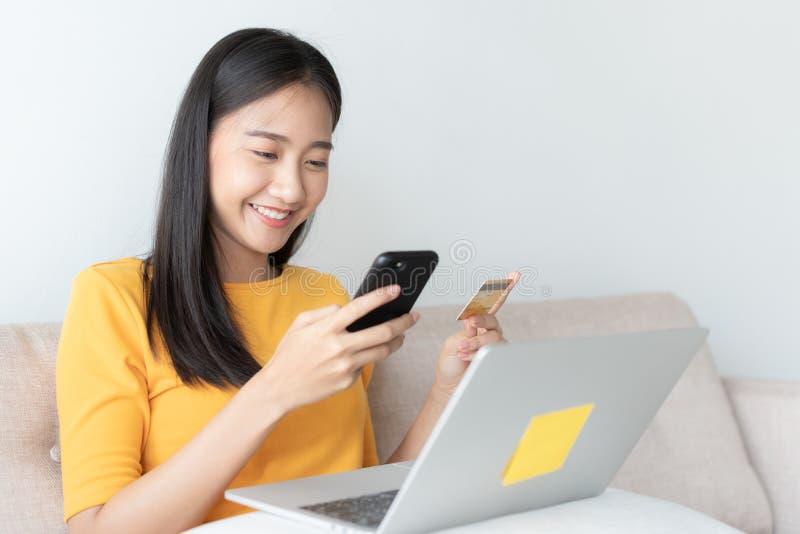 El retrato de mujeres asiáticas jovenes hermosas está comprando en línea con una tarjeta de crédito la muchacha de Asia está util imagen de archivo