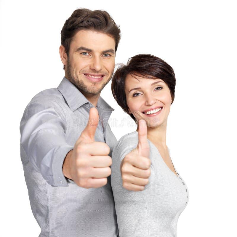 El retrato de pares felices con los pulgares sube la muestra imagen de archivo libre de regalías