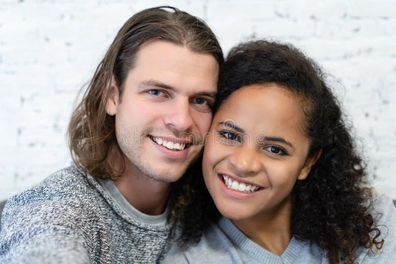 El retrato de pares multi?tnicos jovenes es de abrazo y de goce pasando el tiempo junto mientras que se sienta en el sof? y hace  fotografía de archivo libre de regalías