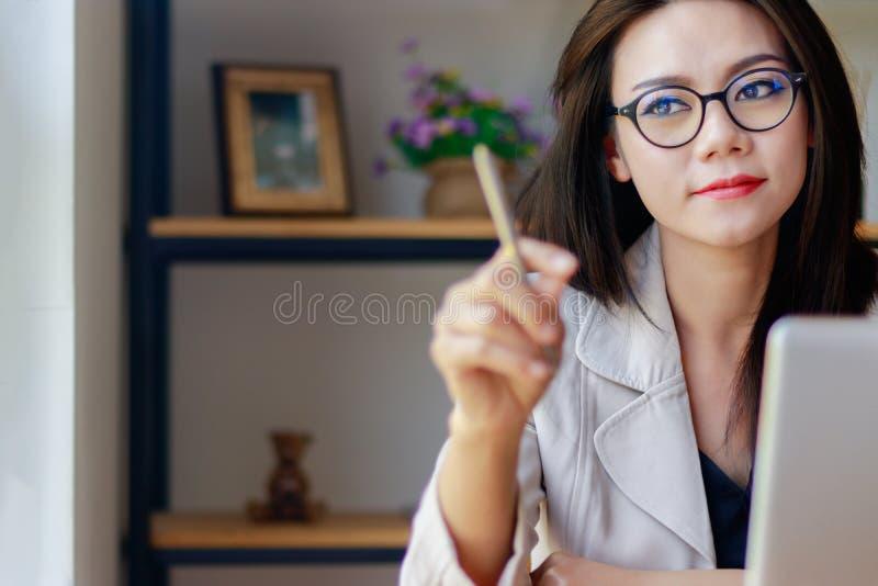 El retrato de relaja a la mujer asiática joven con la cara de la sonrisa que se sienta en oficina foto de archivo libre de regalías
