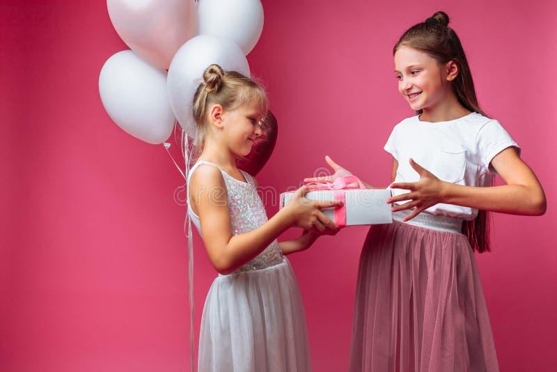 El retrato de un adolescente en un fondo rosado, con los regalos, el concepto del cumpleaños, uno da a otra muchacha un regalo fotos de archivo libres de regalías