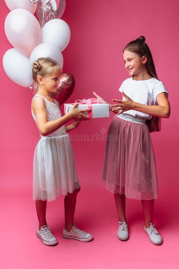 El retrato de un adolescente en un fondo rosado, con los regalos, el concepto del cumpleaños, uno da a otra muchacha un regalo foto de archivo