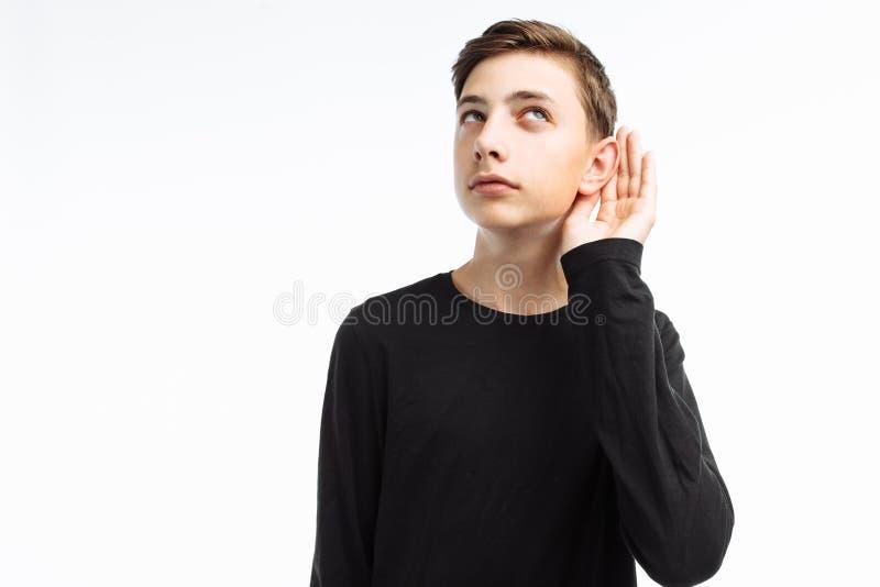 El retrato de un adolescente hermoso, individuo curioso escucha, hace un h foto de archivo libre de regalías