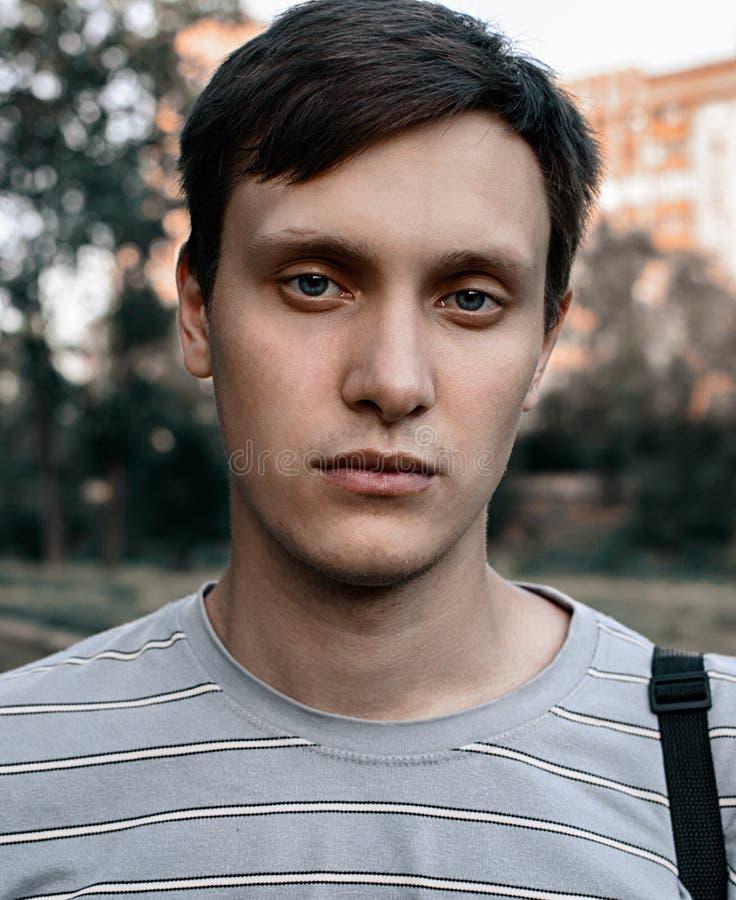 El retrato de un azul joven observó a hombres en el parque imagen de archivo libre de regalías