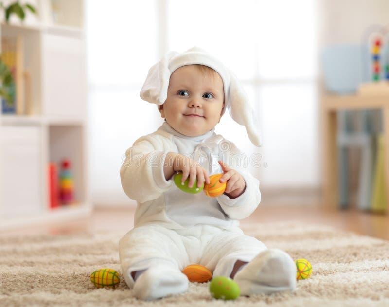 El retrato de un bebé lindo se vistió en traje del conejito de pascua con los huevos en manos foto de archivo