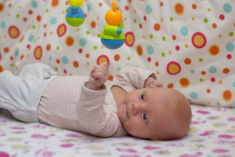 El retrato de un bebé recién nacido lindo que mienta en el suyo detrás en pesebre y juegos con una ejecución juega fotografía de archivo libre de regalías