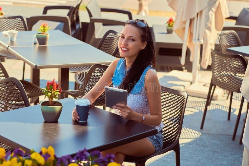 El retrato de un blogger hermoso feliz que la muchacha que lleva la ropa de moda sostiene una tableta está disfrutando de día de  imagenes de archivo