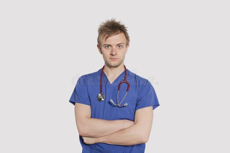 El retrato de un cirujano de sexo masculino serio que se colocaba con los brazos cruzó sobre fondo gris fotos de archivo libres de regalías