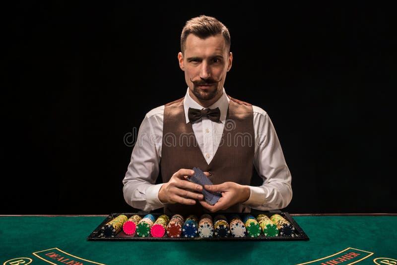 El retrato de un crupié está sosteniendo los naipes, jugando salta en la tabla Fondo negro imágenes de archivo libres de regalías