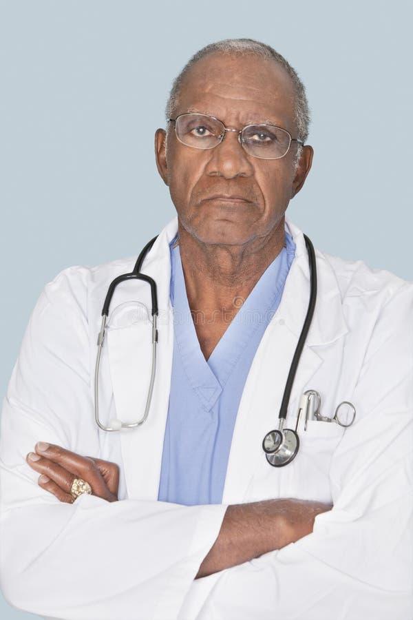 El retrato de un doctor mayor con los brazos cruzó sobre fondo azul claro foto de archivo libre de regalías