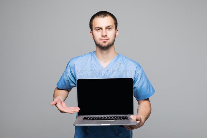 El retrato de un doctor de sexo masculino feliz se vistió en uniforme con el estetoscopio que mostraba el ordenador portátil de l imagen de archivo
