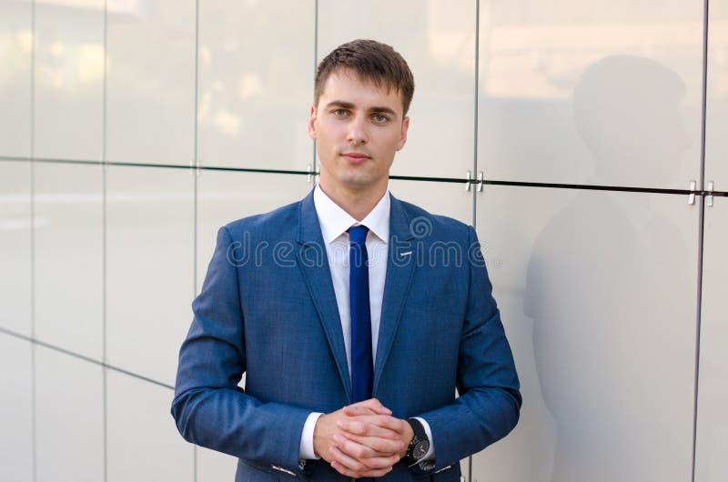 El retrato de un economista acertado joven del hombre que se colocaba en la oficina moderna interior, varón confiado se vistió en fotografía de archivo